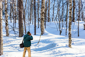 Photographer in winter forest in Arctic