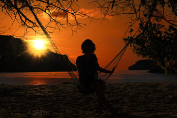 Woman lying on a hammock by the beach at sunset and red sky