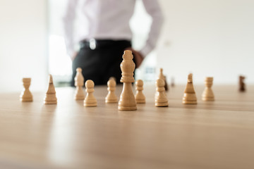Chess pieces with king in the leading position placed on office desk