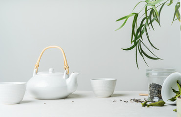 Asian tea concept, two white cups of tea and teapot surrounded with green tea dry leaves , space for a text on white background. Brewing and Drinking tea.