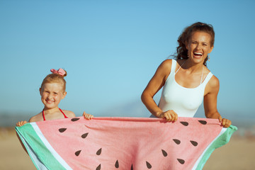 smiling mother and daughter showing funny watermelon towel