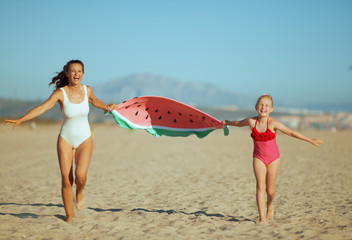mother and child holding funny watermelon towel and running