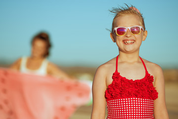 happy girl and mother in background on ocean shore in evening