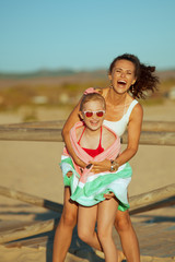 mother and daughter on seacoast in evening having fun time