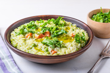 Traditional Italian vegetarian risotto with peas, carrots and parsley in rustic style, closeup