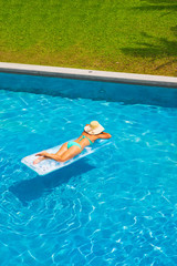 Woman relaxing at the swimming pool at the luxury resort