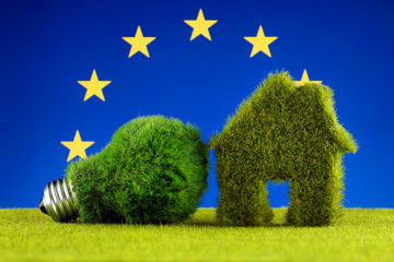 Green eco light bulb, eco house icon and European Union Flag. Renewable energy. Electricity prices, energy saving in the household.
