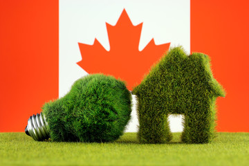 Green eco light bulb, eco house icon and Canada Flag. Renewable energy. Electricity prices, energy saving in the household.
