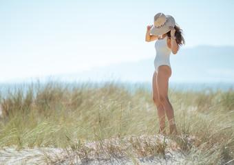 modern woman in white swimsuit on ocean coast wearing hat
