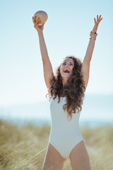 happy modern woman with coconut rejoicing on ocean coast