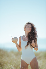 modern woman with coconut with straw on seacoast