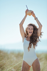 happy modern woman showing coconut with straw on ocean coast