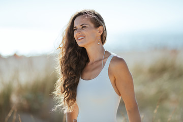 smiling modern woman on seashore looking into distance