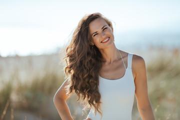 Portrait of happy modern woman in white swimsuit on seashore