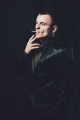 a young man smokes a cigarette, a black background, a classic black suit