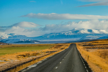 Long Road in iceland with snow mounrtain background
