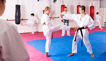 Kids in kimonos exercising techniques in pair during taekwondo class at gym