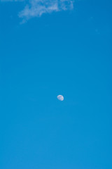 A beautiful moon on a daytime blue, magical sky with white clouds