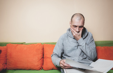 Young or middle age sick man in the casual clothes reading medic results on the papers from his doctor and realize that he have a cancer or other sickness