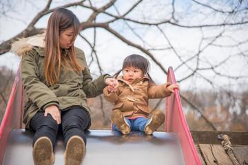 滑り台で遊ぶ親子