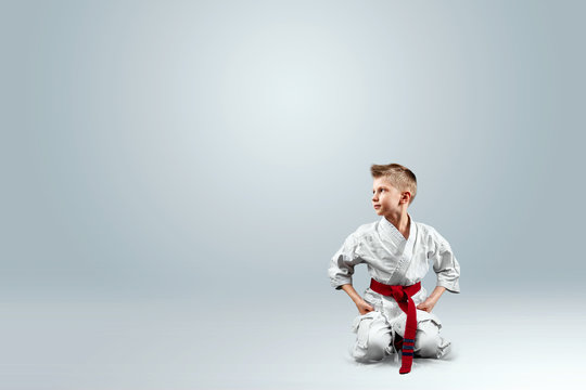 Creative background, baby in white kimono on a light background. The concept of martial arts, karate, sports since childhood, discipline.