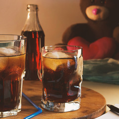 Pepsi-cola in a glass with ice on the background of a burning candle and a teddy bear.