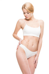 young woman in white underwear looking at correcting marks on body isolated on white