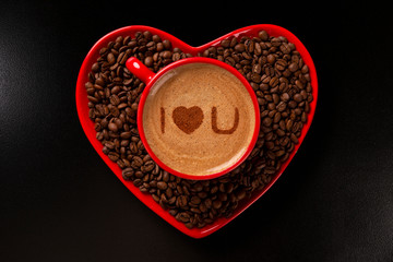 Red cup and coffee saucer in heart shape with decorated coffee on black background. Top View. Written i love you shape in coffee in english.