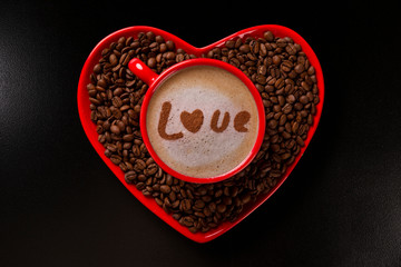 Red cup and coffee saucer in heart shape with decorated coffee on black background. Top View. Written love shape in coffee in english