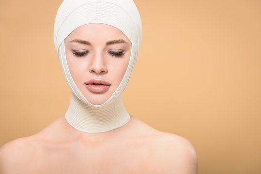 naked young woman with bandages over head looking down isolated on beige