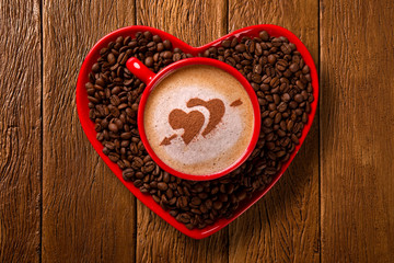 Red cup and coffee saucer in heart shape with decorated coffee on old wood background. Top View. Heart shape in coffee.
