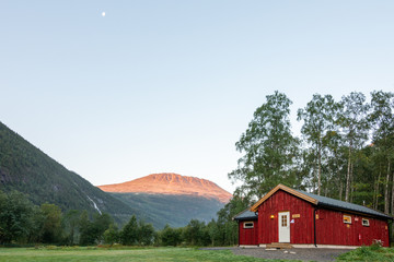 Gaustatoppen in the morning with red hut in the campsite