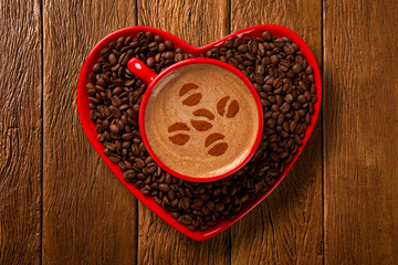 Red cup and coffee saucer in heart shape with decorated coffee on old wood background. Top View. grain shape in coffee.