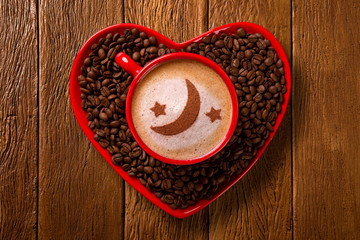 Red cup and coffee saucer in heart shape with decorated coffee on old wood background. Top View. moon and star shape in coffee.