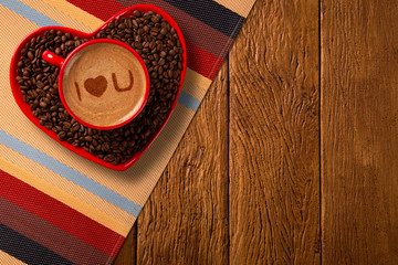 Red cup and coffee saucer in heart shape with decorated coffee on old wood background. Top View. Written i love you shape in coffee in english.
