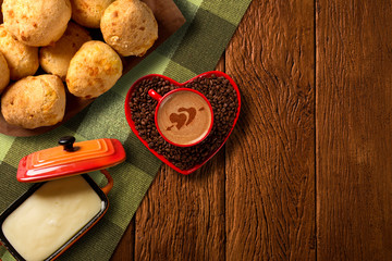 Cheese buns and Red cup and coffee saucer in heart shape with decorated coffee on old wood background. Top View. Heart shape in coffee.