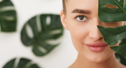 Woman with natural make up and green leaf Wall mural