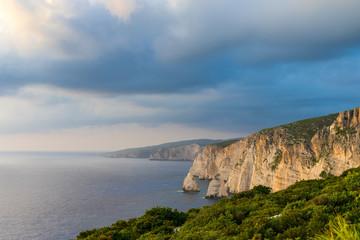 Greece, Zakynthos, Huge white chalk rock wall cliffs alon coastline of the island at sunset
