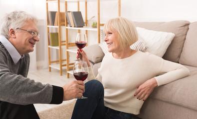 Senior couple enjoying glass of wine at home