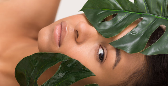 Natural beauty. Woman with green tropical leaves