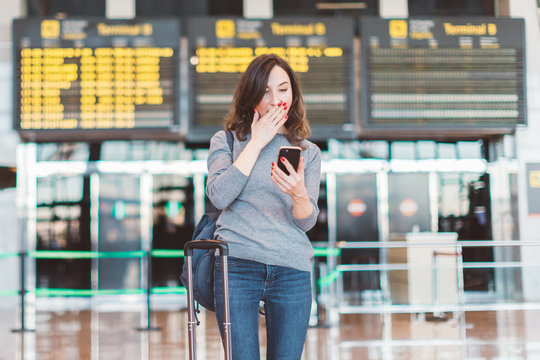 Image of excited, shocked young beautiful woman, standing in airport with smartphone in her hands - missed or cancelled flight concept - flight information board in background