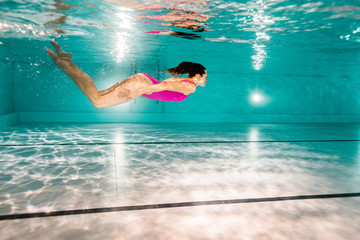 woman diving in blue water in swimming pool