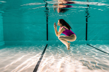 attractive woman posing while diving underwater in swimming pool