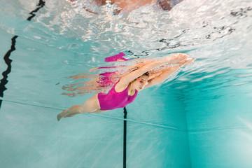 woman swimming in googles underwater in swimming pool