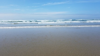 ocean water and sand at the beach in Newport, Oregon