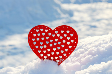 Valentines Day red heart in winter in the snow. Red wooden heart, winter scene with love message.