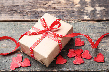 Gift box with ribbon bow and red hearts on grey wooden table