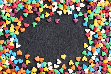 Colorful heart shaped sprinkles on black background