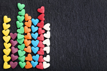 Colorful heart shaped sprinkles in a row on black background
