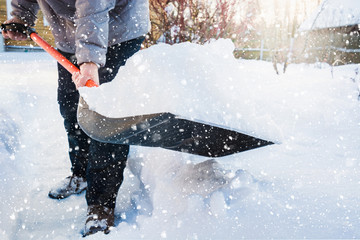 Man clearing snow by shovel after snowfall. Outdoors.